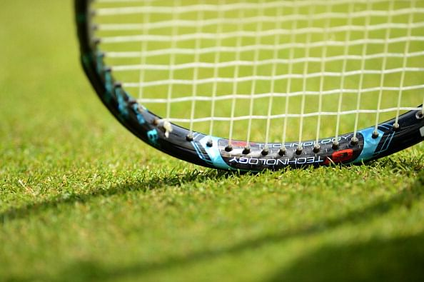 Tennis racket on the grass during the se