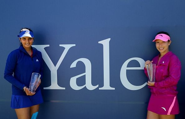 The doubles team of Sania Mirza of India and Jie Zheng of China pose with their championship trophies