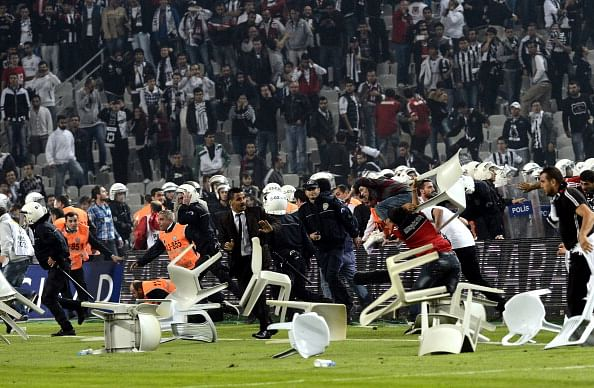 Turkish fans clash with anti-riot police during the match between Besiktas and Galatasaray at the Ataturk stadium