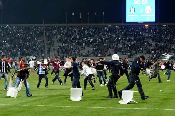 Besiktas football team supporters clash with riot police and security forces during the Turkish Super League soccer match between Besiktas and Galatasaray at the Ataturk Olympic Stadium on Sept. 22, 2013 in Istanbul, Turkey.