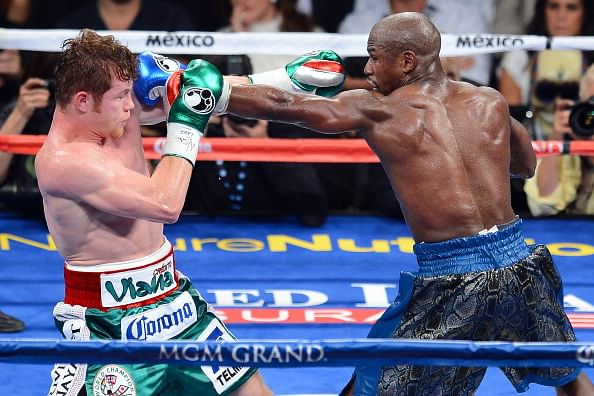 Floyd Mayweather Jr. throws a left at Canelo Alvarez during their WBC/WBA 154-pound title fight at the MGM Grand Garden Arena on September 14, 2013 in Las Vegas, Nevada