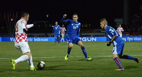 Ivica Olic (L) vies for the ball with Iceland