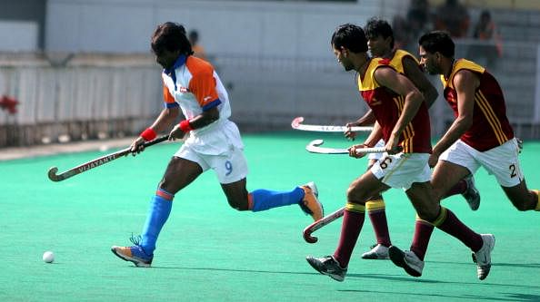 Dhanraj Pillay of Airlines (white) races ahead of PNB players during the 43th Nehru Hockey tournament, New Delhi.