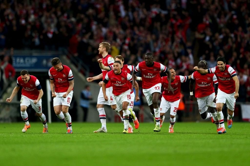 Arsenal players celebrate beating Wigan Athletic to qualify for the finals of the FA Cup