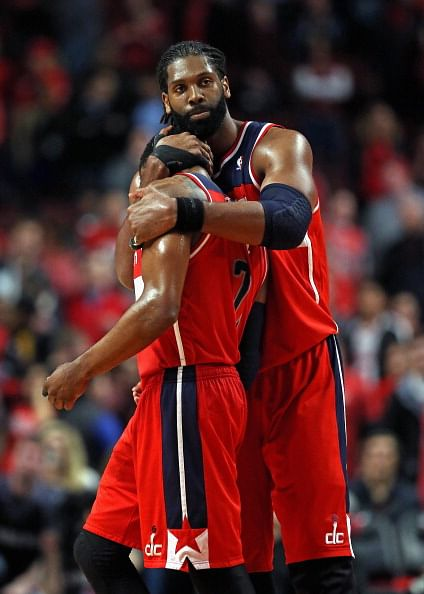 Nene #42 of the Washington Wizards hugs teammate John Wall #2 at the end of the game against the Chicago Bulls in Game Five of the Eastern Conference Quarterfinals during the 2014 NBA Playoffs at the United Center on April 29, 2014 in Chicago, Illinois. The Wizards defeated the Bulls 75-69 to win the series four game to one.