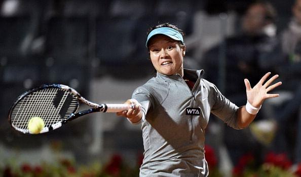 Na Li of China  returns a ball  to Casey Dell