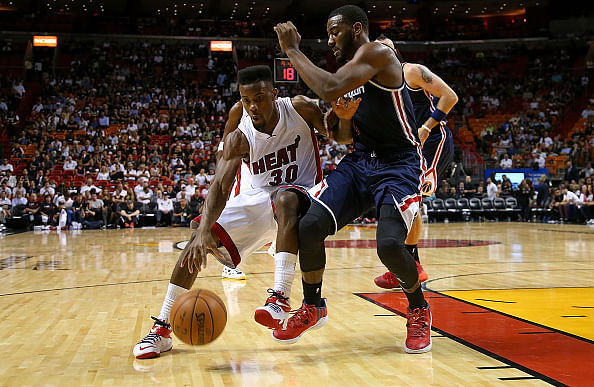 Norris Cole #30 of the Miami Heat drives on John Wall #2 of the Washington Wizards