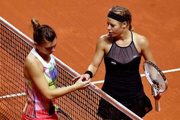 A dejected Simona Halep (left) shakes hands with Laura Siegemund after her loss at Stuttgart on Thursday