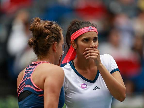 WUHAN, CHINA - OCTOBER 01:  Sania Mirza of India and Barbora Strycova of Czech Republic in action against Lucie Safarova of Czech Republic and Bethanie Mattek-Sands of United States during the double final match of 2016 Dongfeng Motor Wuhan Open at Optics Valley International Tennis Center on October 1, 2016 in Wuhan, China.  (Photo by Kevin Lee/Getty Images)