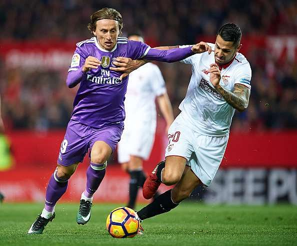 SEVILLE, SPAIN - JANUARY 15:  Luka Modric of Real Madrid CF (L) competes for the ball with Victor Machin Perez