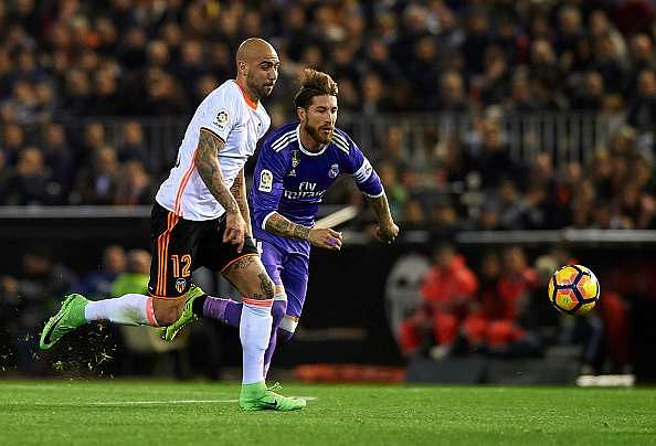 VALENCIA, SPAIN - FEBRUARY 22:  Simone Zaza (L) of Valencia competes for the ball with Sergio Ramos of Real Madrid during the La Liga match between Valencia CF and Real Madrid at Mestalla Stadium on February 22, 2017 in Valencia, Spain.  (Photo by Manuel Queimadelos Alonso/Getty Images)