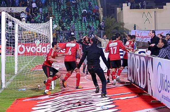 Egyptian Al-Ahly players escape from the field as fans of Al-Masry team