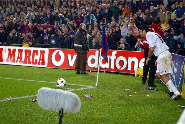 BARCELONA - NOVEMBER 23:  Luis Figo of Real Madrid is bombarded by missiles as he attempts to take a corner during the La Liga match between FC Barcelona and Real Madrid played at the Nou Camp Stadium, Barcelona, Spain on November 23, 2002. (Photo by Firo Foto/Getty Images)