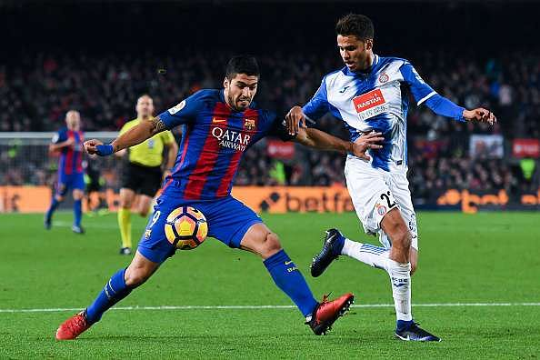 BARCELONA, SPAIN - DECEMBER 18:  Luis Suarez of FC Barcelona competes for the ball with Diego Reyes of RCD Espanyol during the La Liga match between FC Barcelona and RCD Espanyol at the Camp Nou stadium on December 18, 2016 in Barcelona, Spain.  (Photo by David Ramos/Getty Images)