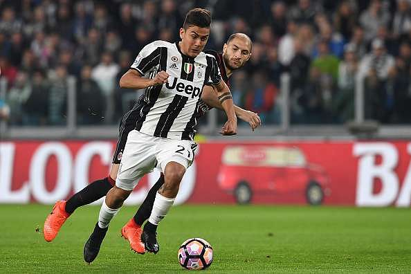TURIN, ITALY - MARCH 10:  Paulo Dybala (L) of Juventus FC in action against Gabriel Paletta of AC Milan during the Serie A match between Juventus FC and AC Milan at Juventus Stadium on March 10, 2017 in Turin, Italy.  (Photo by Valerio Pennicino/Getty Images)
