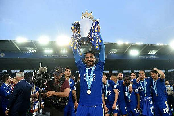 LEICESTER, ENGLAND - MAY 07:  Riyad Mahrez of Leicester City lifts the Premier League Trophy as players and staffs celebrate the season champion after the Barclays Premier League match between Leicester City and Everton at The King Power Stadium on May 7, 2016 in Leicester, United Kingdom.  (Photo by Michael Regan/Getty Images)
