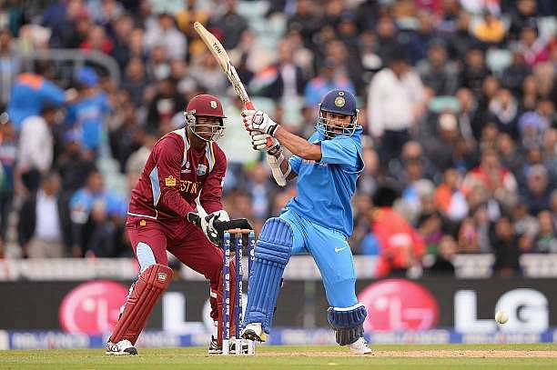 LONDON, ENGLAND - JUNE 11:  Shikar Dhawan of India hits out as wicketkeeper Johnson Charles of West Indies looks onduring the ICC Champions Trophy Group B match between India and West Indies  at The Kia Oval on June 11, 2013 in London, England.  (Photo by Mike Hewitt/Getty Images)