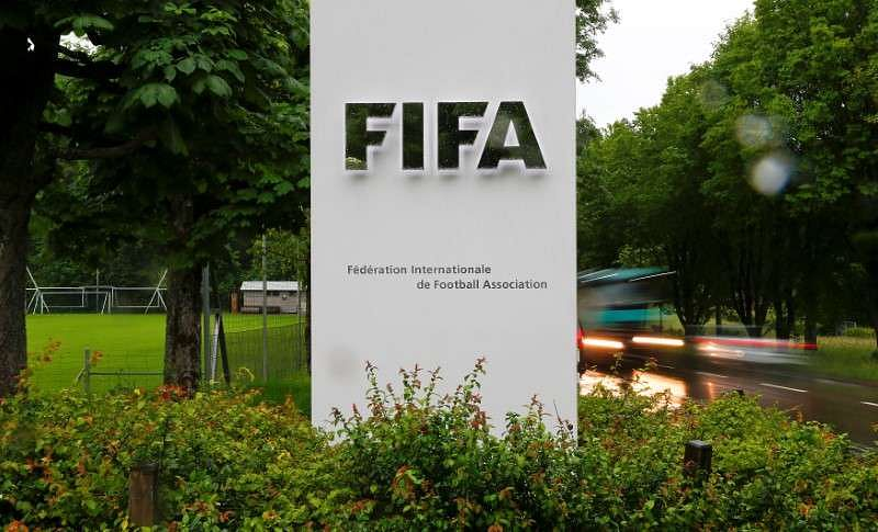Cars drive past a logo in front of FIFA