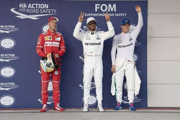 Oct 21, 2017; Austin, TX, USA; Ferrari driver Sebastian Vettel (left) of Germany and Mercedes driver Lewis Hamilton (center) of Great Britain and Mercedes driver Valtteri Bottas (right) of Finland wave to the crowd after qualifying for the United States Grand Prix at Circuit of the Americas. Mandatory Credit: Jerome Miron-USA TODAY Sports